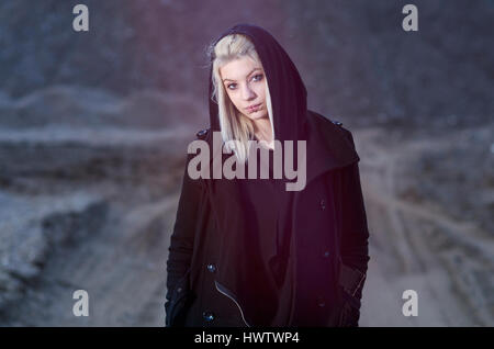 Young female wearing black hood in nature night shot - Stock Photo