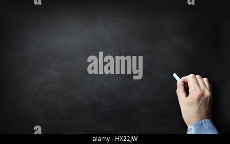 Blank blackboard or chalkboard with hand holding chalk writing on black chalk board - Stock Photo