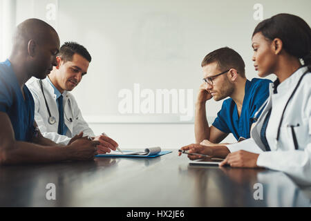 Medical staff meeting. Group of young people in white coats and blue uniform sitting at table in front of each other. - Stock Photo