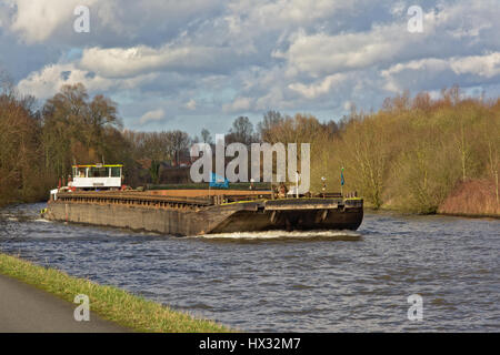 Dry bulk carrying cargo ship on river scheldt in natural environment on a cloudy winter day - Stock Photo