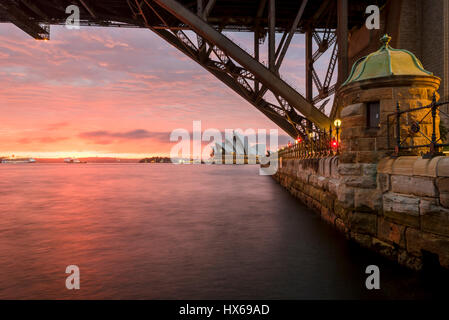 Sydney Opera House at dawn viewed from under the Sydney Harbor Bridge - Stock Photo