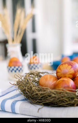 Traditionally dyed Easter eggs using onion skins, flowers and plants - Stock Photo