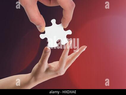 Digital composite of Hands holding jigsaw piece helping against red background - Stock Photo