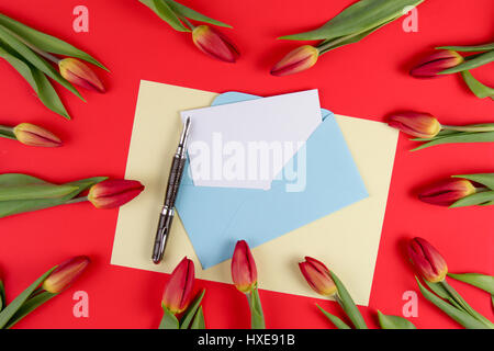 Blank card, pen, blue envelope and red spring tulips flowers on red background. Top view. Flat lay - Stock Photo