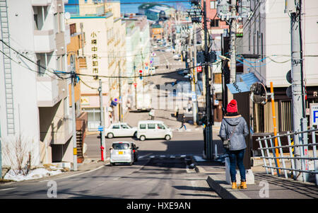 Red hat girl glance at sea in Funemizaka Otaru Japan - Stock Photo