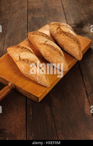 Loaves of rye bread on rustic board - Stock Photo