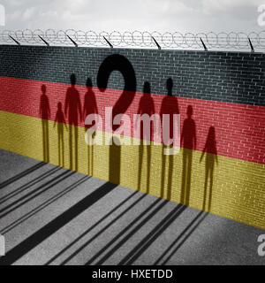 German refugee question and immigration government policy as newcomers in Germany as the cast shadow on a wall with - Stock Photo