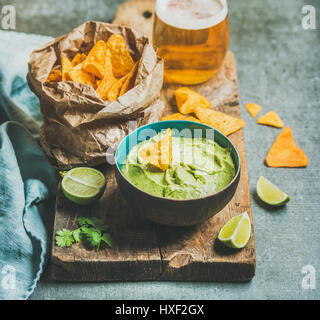 Fresh guacamole sauce in blue ceramic bowl, corn chips, beer - Stock Photo