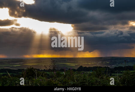 Just before sunset. Light rays shining through the stormy clouds and hitting Bodmin Moor, Cornwall, down below. - Stock Photo