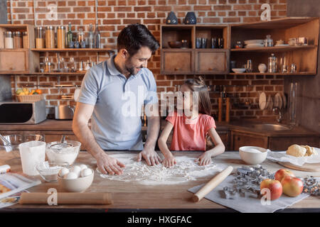 'Happy father and daughter cooking together and looking at each other in kitchen - Stock Photo