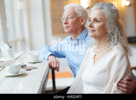 Mature man embracing his spouse while looking through window in cafe - Stock Photo