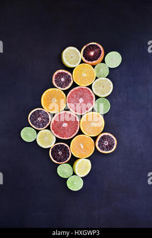 Variety of citrus fruits (orange, blood oranges, lemons, grapefruits, and limes) over a black rustic background. - Stock Photo