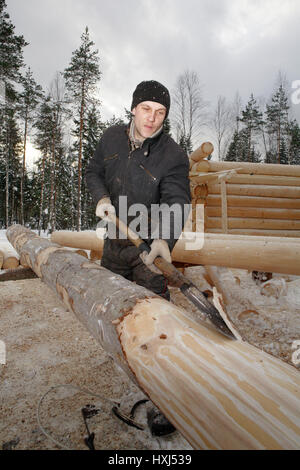 Leningrad Region, Russia - February 2, 2010: The process of peeling and debarking of wood, Worker hand peeled logs - Stock Photo