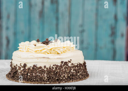 White frosted cake with chocolate at the bottom - Stock Photo