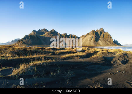 Stokksnes sand dunes and Vestrahorn mountains in late afternoon Autumn light on a clear sunny day, Iceland - Stock Photo