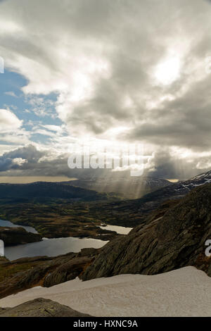 Rays of light shining through clouds in a mountainous landscape in the north of Norway - Stock Photo