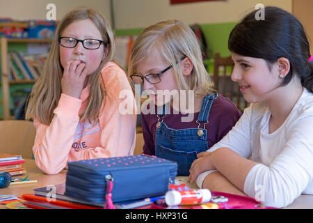 three girls working together at primary school - Stock Photo