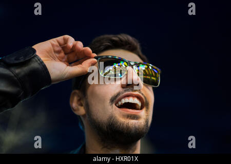 Smiling man in sunglasses with colorful reflection of night lights. Night city life - Stock Photo