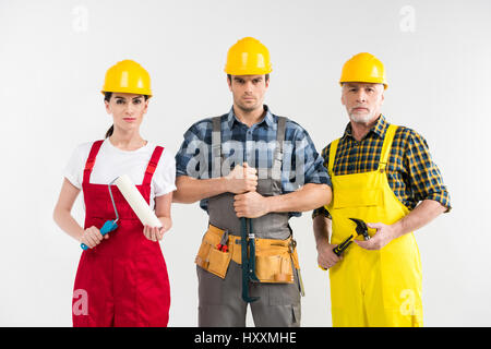 Professional construction workers holding tools and looking at camera - Stock Photo