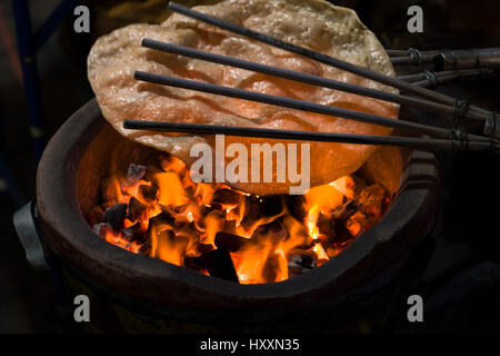 Traditional Thai rice flour snack cooking over fire and hot coals. - Stock Photo