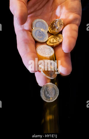 pound coins falling from man's hand - Stock Photo