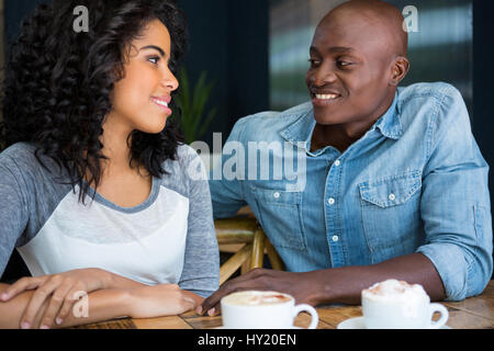 Loving young couple looking at each other at table in coffee shop - Stock Photo