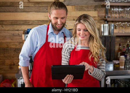 Smiling male and female baristas using digital tablet in coffee shop - Stock Photo