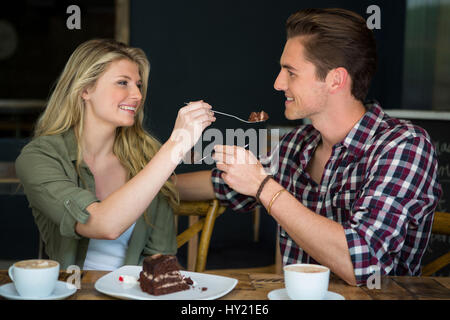 Smiling young couple feeding each other dessert in cafe - Stock Photo