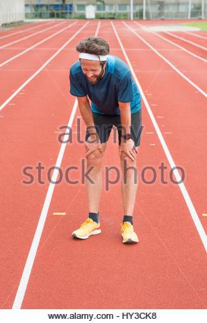 Sweden, Skane, Malmo, Athlete standing on track - Stock Photo