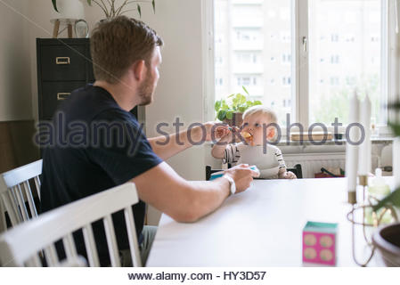 Sweden, Father helping son (12-17 months) eating at table - Stock Photo