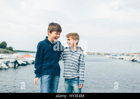 Sweden, Blekinge, Karlskrona, Boys (8-9) standing next to marina and laughing - Stock Photo