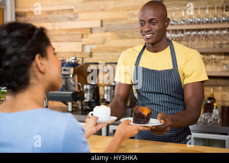 Portrait of male barista serving coffee and dessert to female customer in cafe - Stock Photo