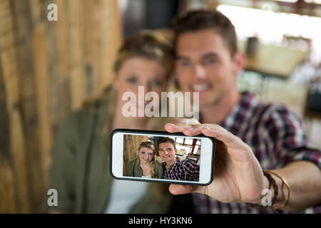 Smiling young couple taking selfie with cellphone in cafeteria - Stock Photo