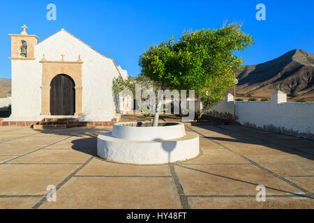 Well on courtyard of Typical white Canary style church in Tefia village and volcano mountain in background, Fuerteventura, - Stock Photo