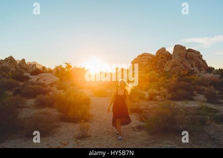 USA, California, Joshua Tree National Park, Woman wearing dress hiking at sunset - Stock Photo