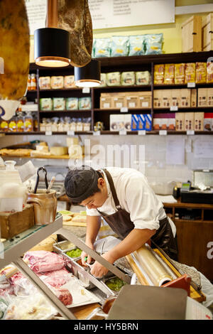 Sweden, Young man working in store - Stock Photo