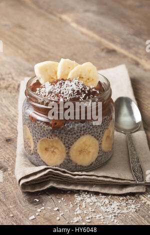 chia pudding with chocolate banana smoothie in a glass jar on the old wooden background - Stock Photo