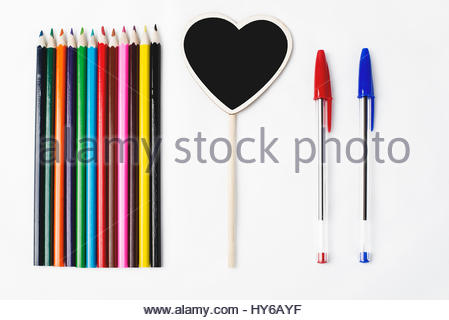 Wooden pencils two pens and a small blackboard with heart shape on white background - Stock Photo