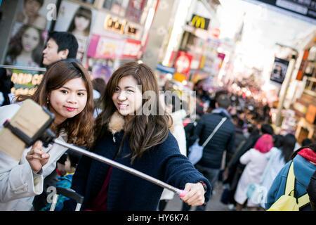 Tokyo, Japan - January 10, 2017: Japanese tourists girls are taking selfie in front of Takeshita Street in Harajuku, - Stock Photo