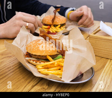 Man eating burger with bacon with fried potatoes and drinking tea. Street fast food. - Stock Photo