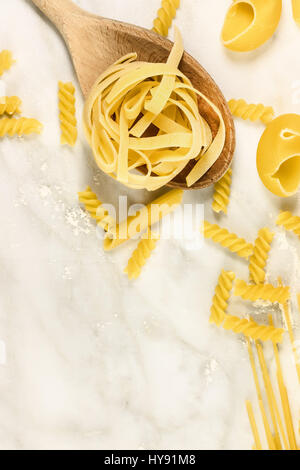Various types of pasta on marble with copyspace - Stock Photo