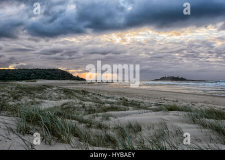 Atmospheric sky at sunrise over Conjola Beach, Shoalhaven, South Coast, New South Wales, NSW, Australia - Stock Photo