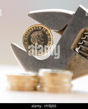 New One Pound £1 coin held in an adjustable spanner against a light background with coins stacked up in the foreground - Stock Photo