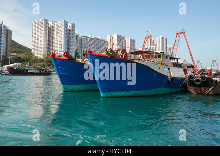 Brightly Painted Commercial Fishing Boats Moored In Aberdeen Channel, High Rise Apartment Buildings On Ap Lei Chau - Stock Photo