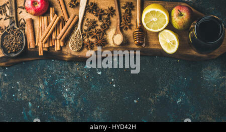Ingredients for making mulled wine. Wine in glass bottle, honey, lemon, apples and spices on wooden board over old - Stock Photo