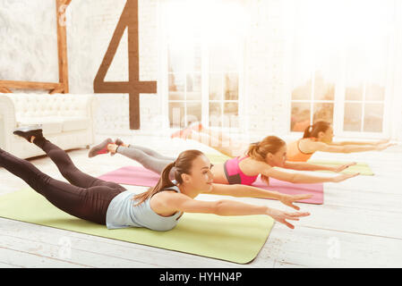 Youthful women lying on floor and stretching - Stock Photo