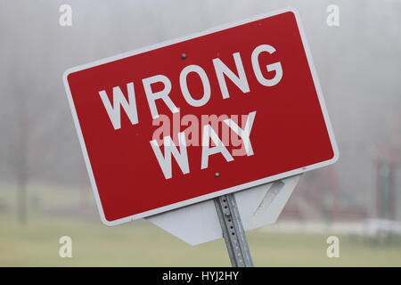 Bowed rectangular red road sign with the inscription 'wrong way' mounted on a metal support. Road sign prohibiting - Stock Photo