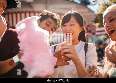 Group of friends eating candyfloss at amusement park. Smiling young people sharing cotton candy outdoors. - Stock Photo