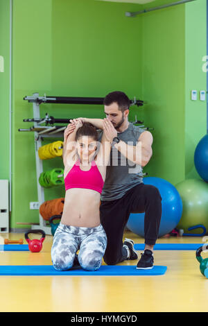 Young woman working out with personal trainer at the gym. - Stock Photo