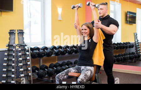 Working out in gym: Beutiful yong woman doing dumbbell excercise sitting on bench while muscular trainer watching - Stock Photo